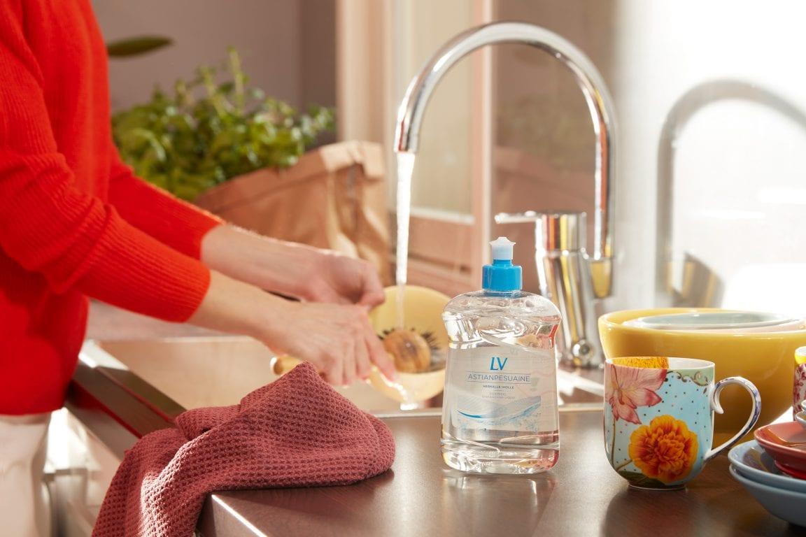 Nainen pesee astioita. Etualalla keittiöpyyhe ja LV Astianpesuaineen pakkaus.
