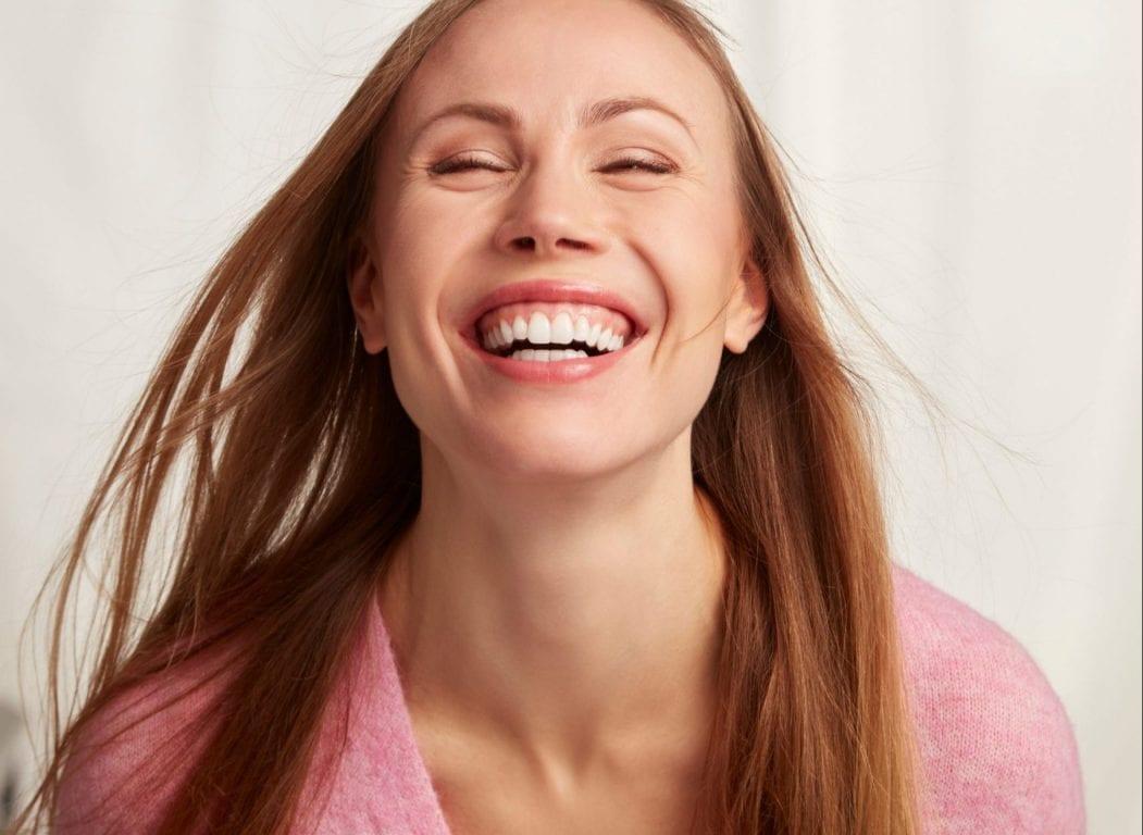 Nainen nauraa iloisesti kameralle