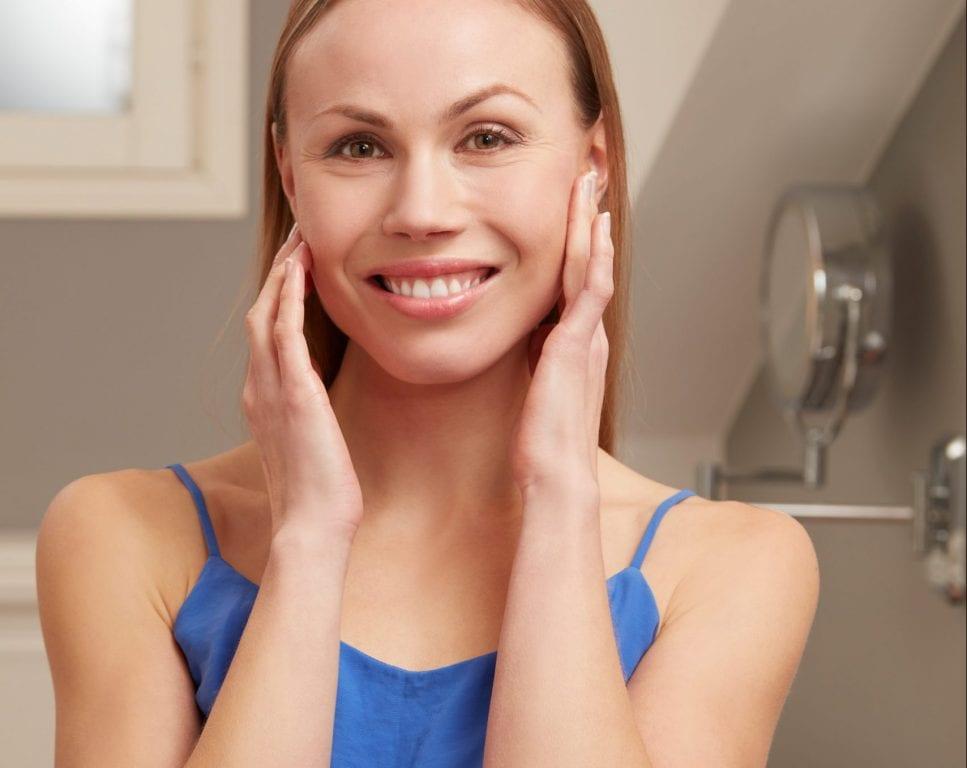 Nainen koskettaa kasvojaan hymyillen kylpyhuoneessa meikkipeilien edessä.