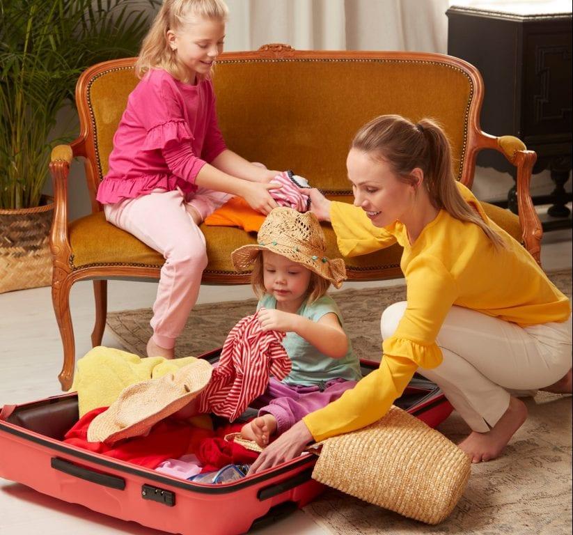 Äiti ja kaksi tytärtä pakkaavat matkalaukkua. Tytöistä pienin istuu matkalaukussa.