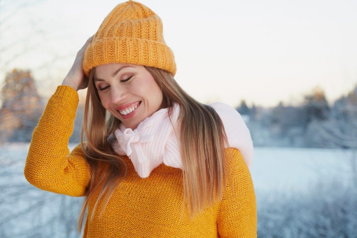 Keltaiseen pipoon ja villapaitaan pukeutunut nainen hymyilee ulkona. Taustalla sumeana talvinen maisema.