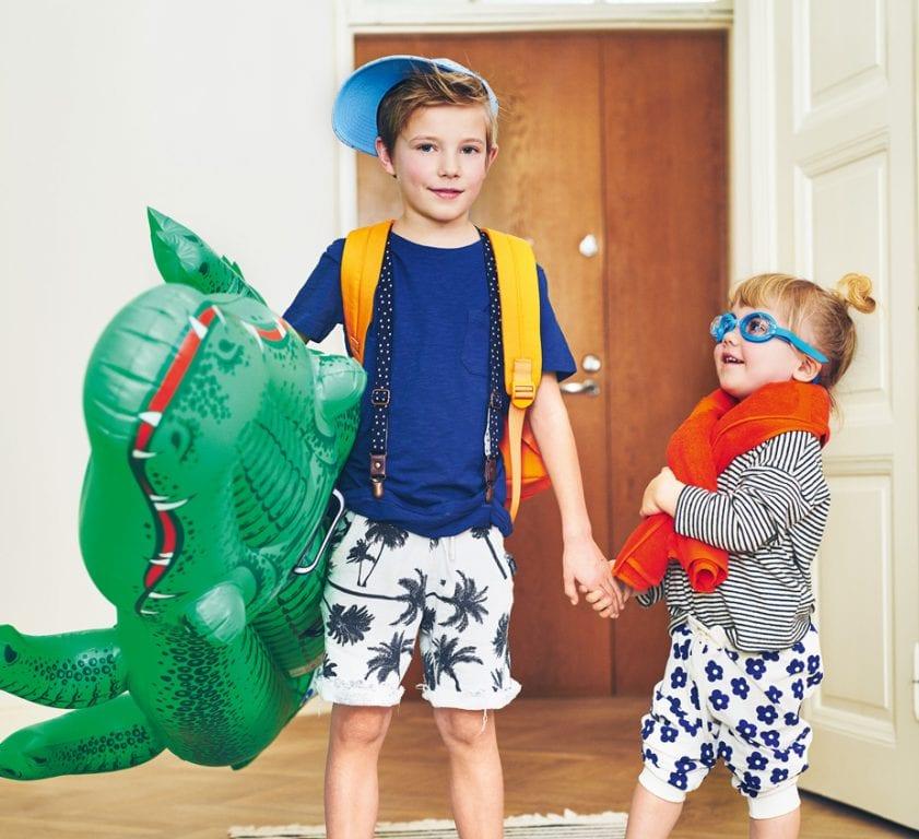 Poika ja tyttö kodin eteisessä lähdössä rannalle. Tytöllä päässä uimalasit ja pojalla kainalossa krokotiiliuimapatja, jalassa mustat räpylät ja päässä sininen lippis.
