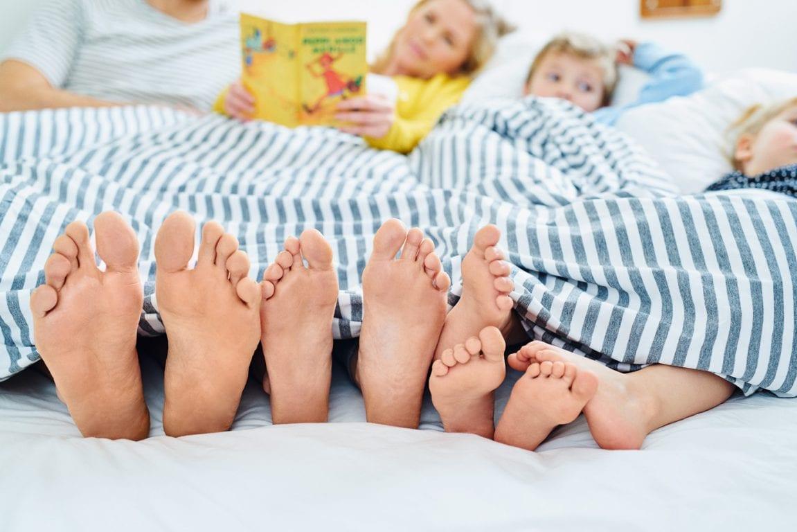 Perhe sängyssä yhden ison peiton alla jalkapohjat kameraan päin varpaat kattoa kohti.