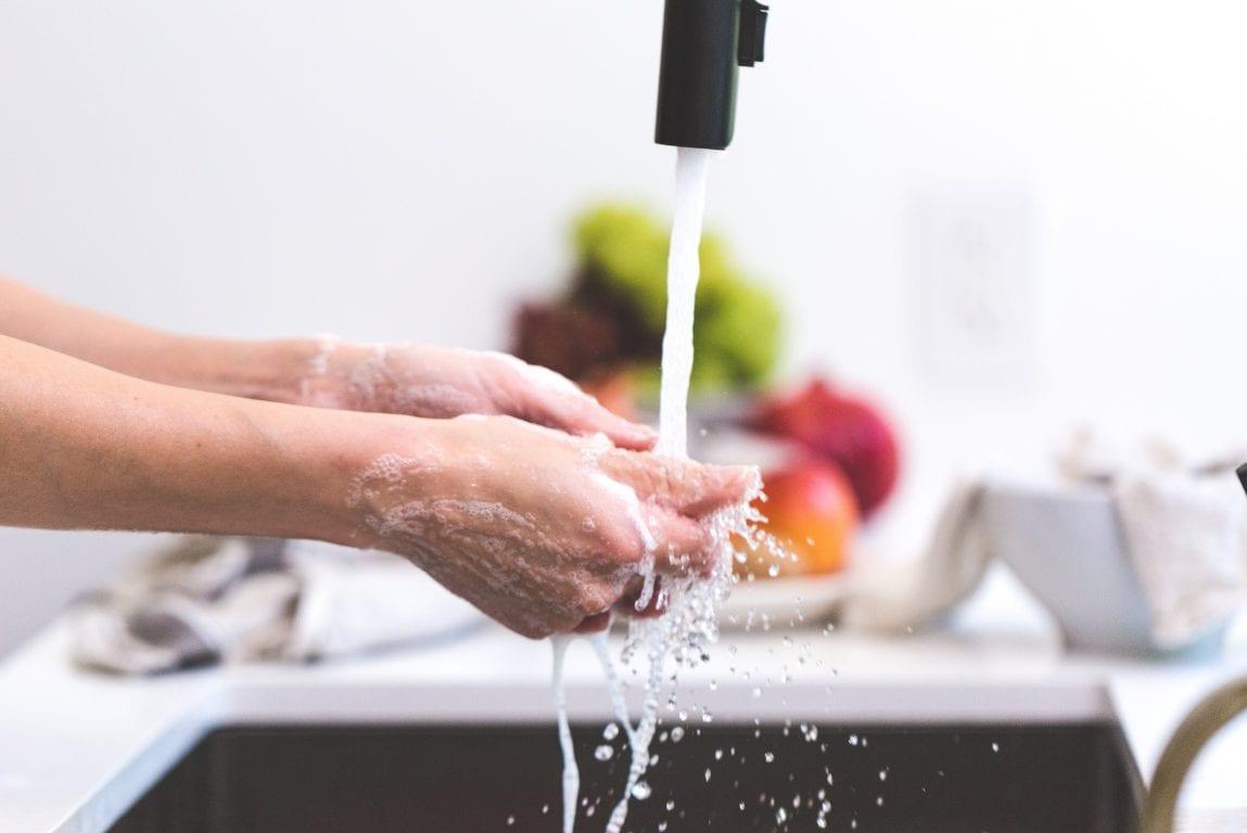 Mies pesee käsiään saippualla juoksevan veden alla.
